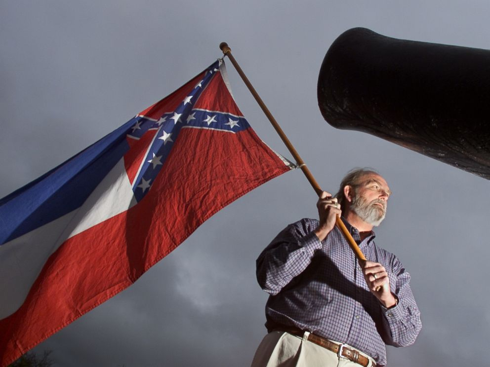 PHOTO: In this file photo taken on Dec. 12, 2001, Harry Sharp proudly holds the Mississippi State flag in the centre of Vicksberg Miss.