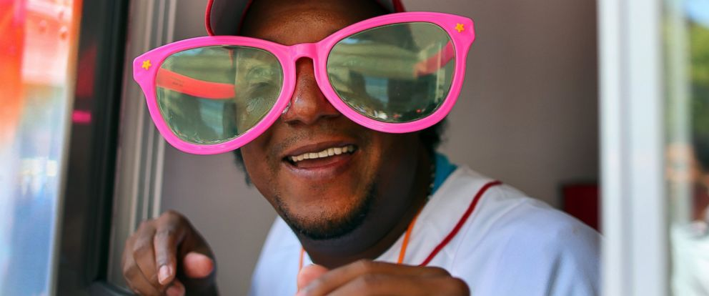 """PHOTO: Former Red Sox pitcher Pedro Martinez wears some big glasses given to him by a fan as he gave out Good Humor ice cream from their truck parked across from the Copley T station as part of the """"Share the Love"""" campaign."""