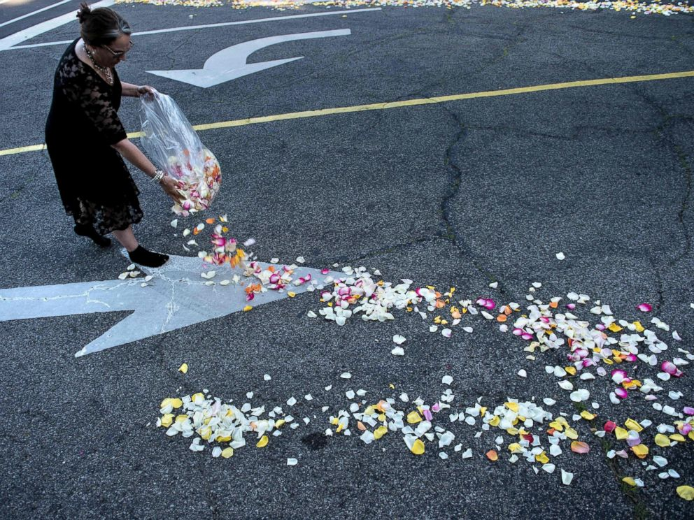 PHOTO: A woman places flower petals along the entrance to Cave Hill Cemetery for the funeral procession for boxing legend Muhammad Ali on June 10, 2016 in Louisville, Kentucky.