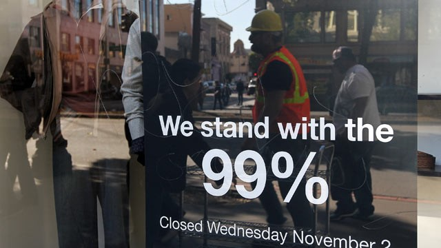 PHOTO: A sign hangs in the window of a Men's Wearhouse store in solidarity with Occupy Oakland's general strike, Oakland, California, Nov. 2, 2011.