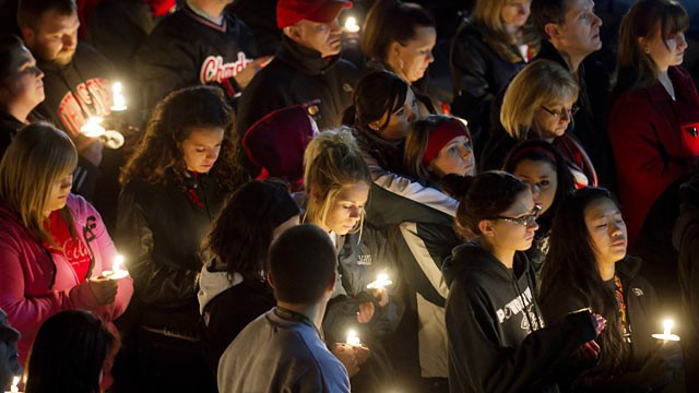PHOTO: Students and those in the community embrace one another as they hold a candlelight vigil at St Mary's of the Assumption Church.
