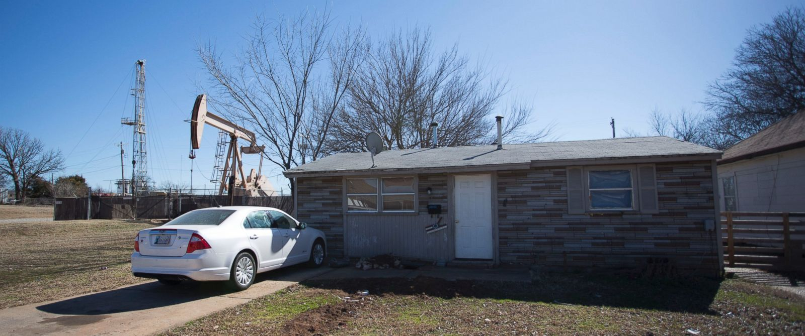 PHOTO: A new fracking rig and a pumping rig stand beside a house on February 10, 2016 in an Oklahoma City, Oklahoma neighborhood.