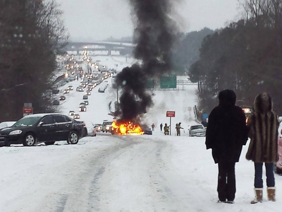 PHOTO: Motorists watch a vehicle burn after it caught fire while struggling to get up a snow covered hill in Raleigh, North Carolina on February 12, 2014.