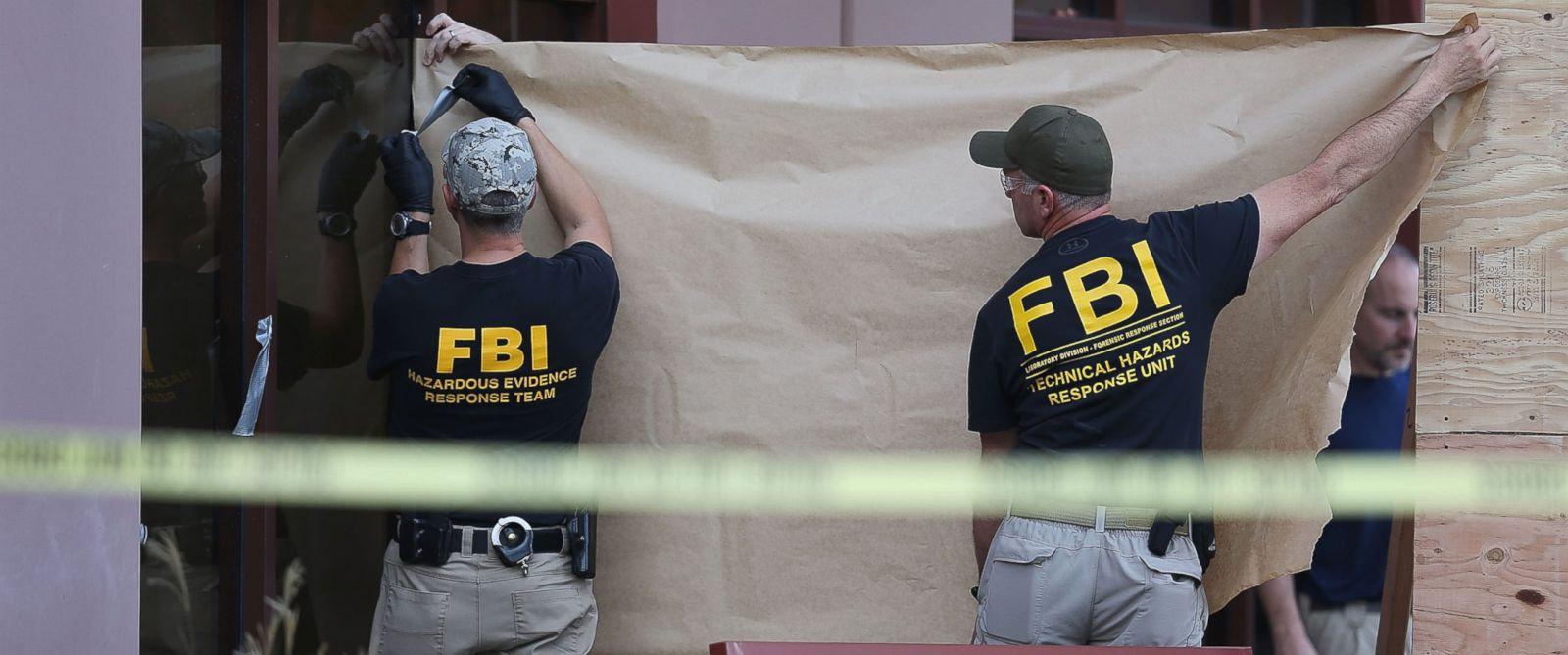 PHOTO: FBI agents put up a screen to block the view of onlookers as they investigate the building at the Inland Regional Center were 14 people were killed, Dec. 7, 2015 in San Bernardino, Calif.