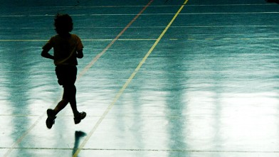 PHOTO: A young boy running on a basketball court.
