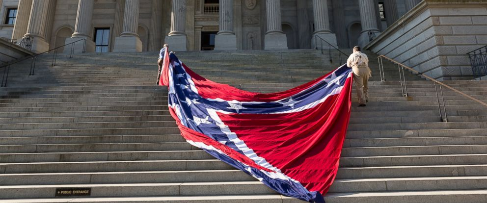 PHOTO: Confederate re-enactors position a gigantic Confederate flag on the steps of the South Carolina State Capitol building on May 2, 2015 in Columbia, SC.