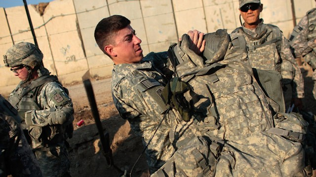 PHOTO: Lt. Andrew Minoski of Las Vegas, Nevada of the U.S. Army's 172nd Brigade Combat Team (C) dons his body armor before a patrol January 19, 2009 in Musayyib, in the Babil Province, Iraq.