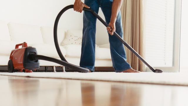 PHOTO: Man vacuuming carpet
