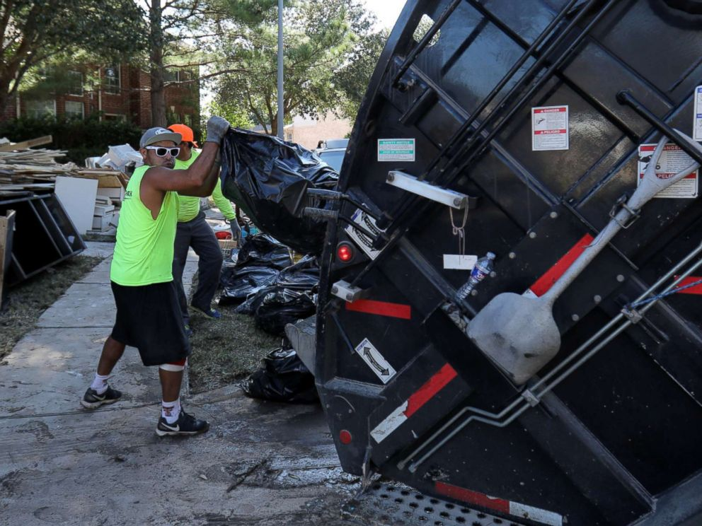 Houston Christmas Tree Pickup Part - 25: PHOTO: A Garbage Truck Helps Residents Remove Bags Of Flood-damaged Items  That Line