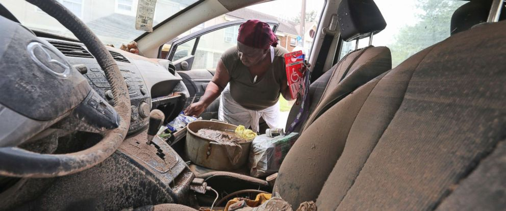 PHOTO: Gillis Leho looks for documents in her car that was covered by floodwaters after Tropical Storm Harvey in Houston, Texas, Aug. 30, 2017.