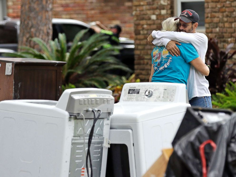PHOTO: Barry Horvitz hugs his wife Kim while standing outside their home after removing items damaged by floodwaters from Tropical Storm Harvey on Aug. 30, 2017, in Houston, Texas.