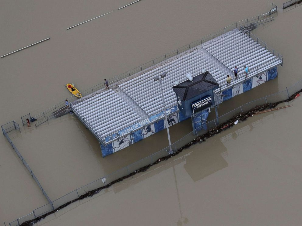 PHOTO: People gather on the bleachers of a flooded high school football field near Lake