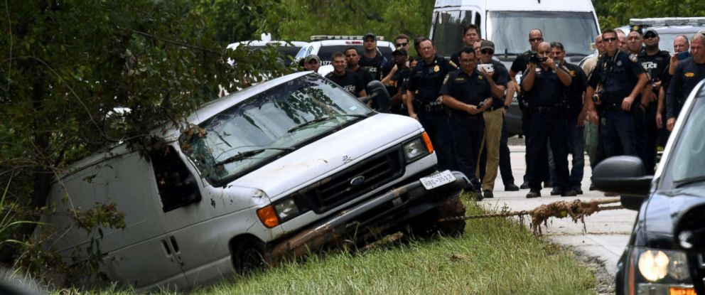 PHOTO: Police investigators watch as the van containing the six members of the the Saldivar family is towed to the road in Houston, Texas on Aug. 30, 2017.