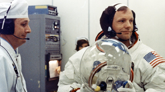 PHOTO: Apollo 11 Commander Neil Armstrong prepares to put on his helmet with the assistance of a spacesuit technician during suiting operations in the Manned Spacecraft Operations Building (MSOB) prior to th