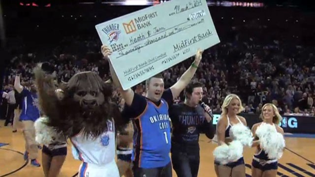PHOTO: Oklahoma City Thunder fan Heath Kufahl shows his $20,000 check after scoring a half court shot, March 5, 2013.