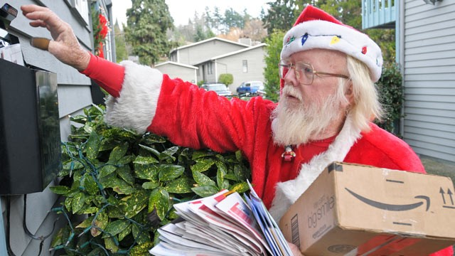 PHOTO: Postal carrier Bob McLean delivers mail, dressed as Santa, in Bellevue, Wash., in this 2009 file photo.