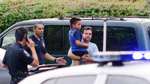 PHOTO: Escorted by Hollywood police, Luis Gutierrez Sr. carries his son Luis Gutierrez Jr. away from their home after a foiled robbery that had Luis Gutierez Jr. pinned beneath his bed until police arrived in Hollywood.