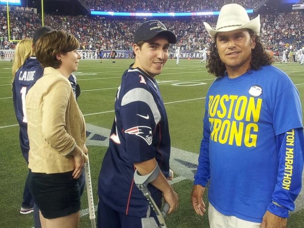 PHOTO: Carlos Arredondo, right, and Jeff Bauman, center, are pictured at a Patriots game against the Jets in Foxborough, Mass.