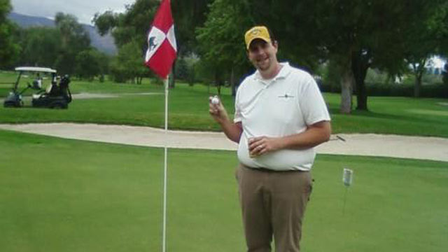 PHOTO: Troy Peissig taking the ball out of the hole after his hole-in-one shot for charity.