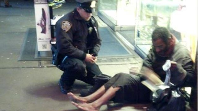 PHOTO: An NYPD officer gives a shoeless homelsess man a pair of boots in New York City, Nov. 27, 2012.