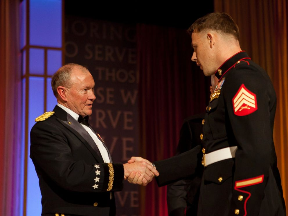 PHOTO: Marine Corps Sgt. Andrew C. Seif, right, shakes hands with the Chairman of the Joint Chiefs of Staff, Army Gen. Martin E. Dempsey, before receiving the USO Marine of the Year award during the 2013 USO Gala in Washington.
