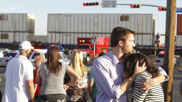 PHOTO: Bystanders react after a flatbed truck carrying wounded veterans and their families during a parade was struck by a train Thursday