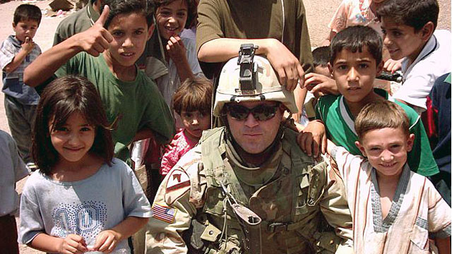PHOTO: Then-Cpt. Troy Denomy poses for a photo with children in Iraq.