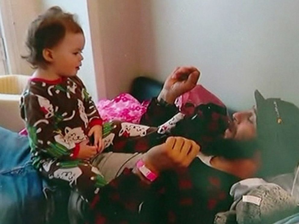 PHOTO: Lily Groesbeck plays with her father, Devin Trafny, in a hospital room on March 11, 2015, in a home video provided by a family member.