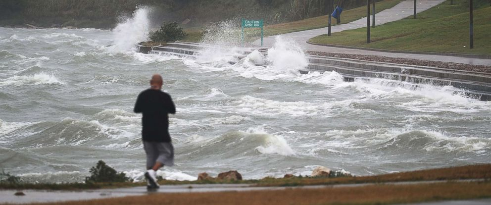 PHOTO: A man walks near the bay waters as they churn from approaching Hurricane Harvey