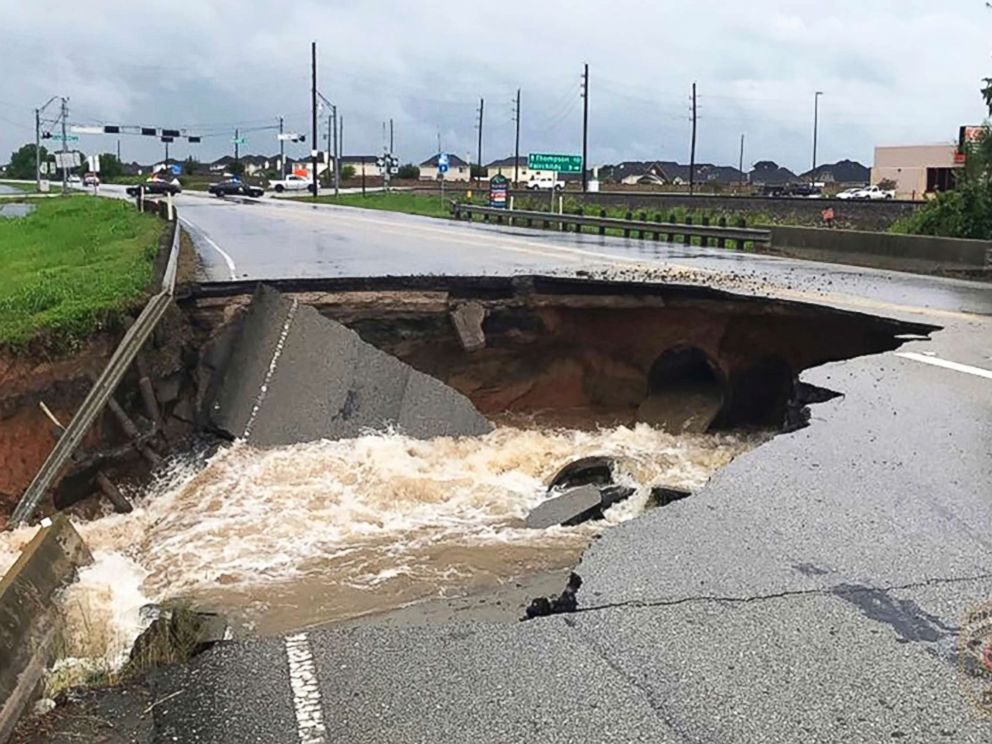 PHOTO: Water rushes from a large sinkhole on Highway FM 762 in Rosenberg, Tx., near Houston, on Aug. 27, 2017.