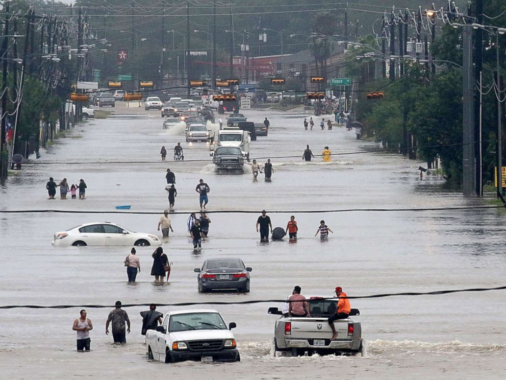 PHOTO: People walk through the flooded waters of Telephone Rd. in Houston on Aug