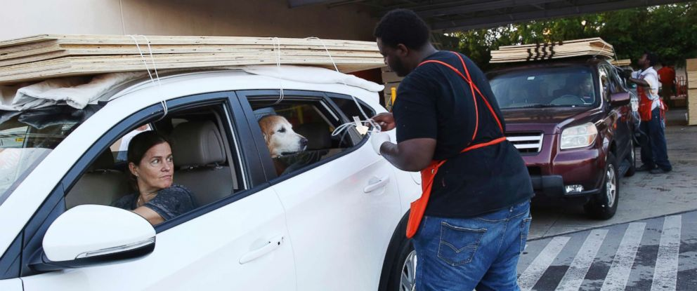 PHOTO: Beatriz Bustamante and her dog Simon wait as Qawrence Symonette secures sheets of plywood on her car at a store in North Miami, Sept. 6, 2017.