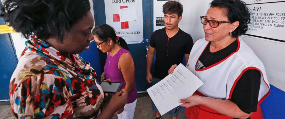 PHOTO: A Red Cross volunteer speaks with people arriving at a Red Cross shelter set up at North Miami Beach Senior High School, Sept. 8, 2017 in North Miami Beach, Fla.