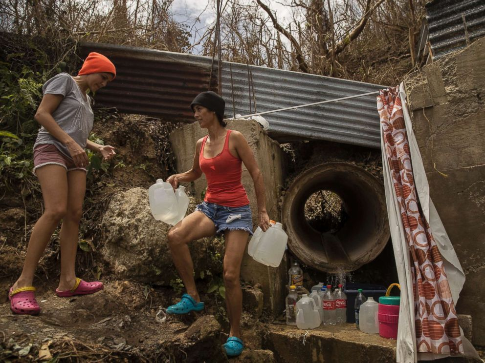 PHOTO: Yamilex Virella and her mother-in-law, Norma Andreu, carry water from a natural spring in the hill town of Toa Alta, Puerto Rico, Sept. 25, 2017.