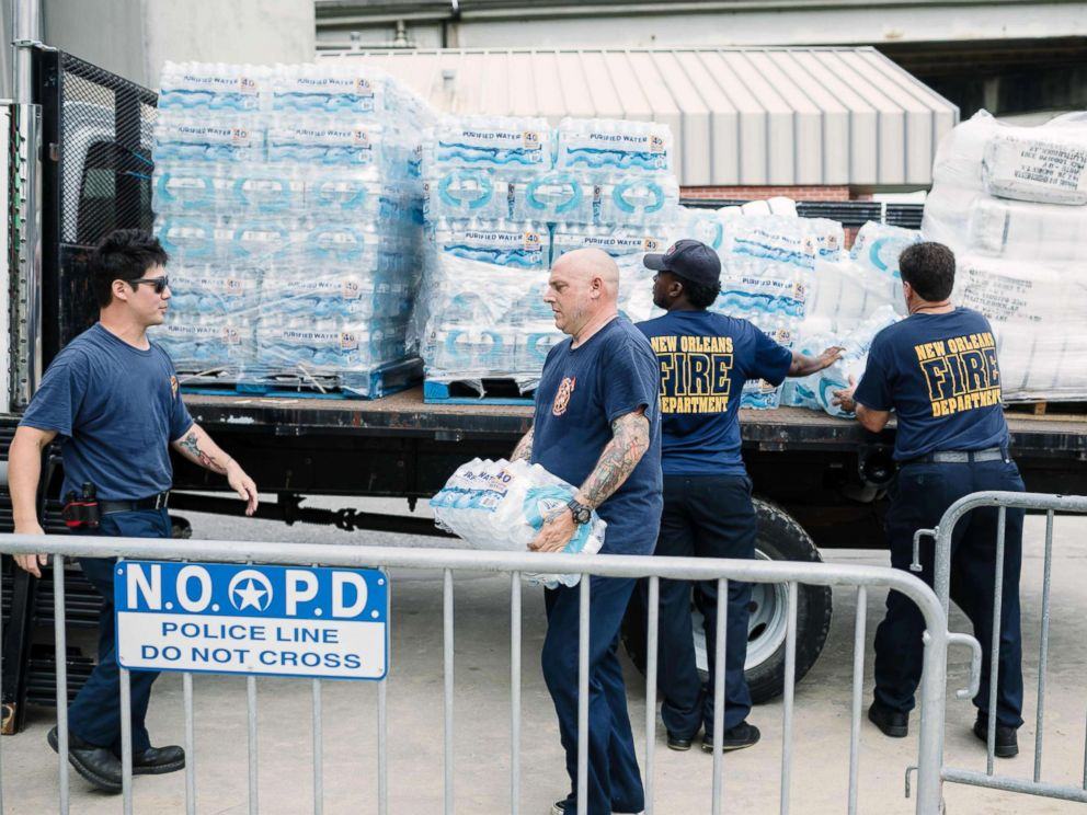 PHOTO: Firefighters Stan Ho (L) and Richard Jensen (C) unload supplies for the people of New Orleans in preparation of Hurricane Nate in New Orleans, Oct. 7, 2017.