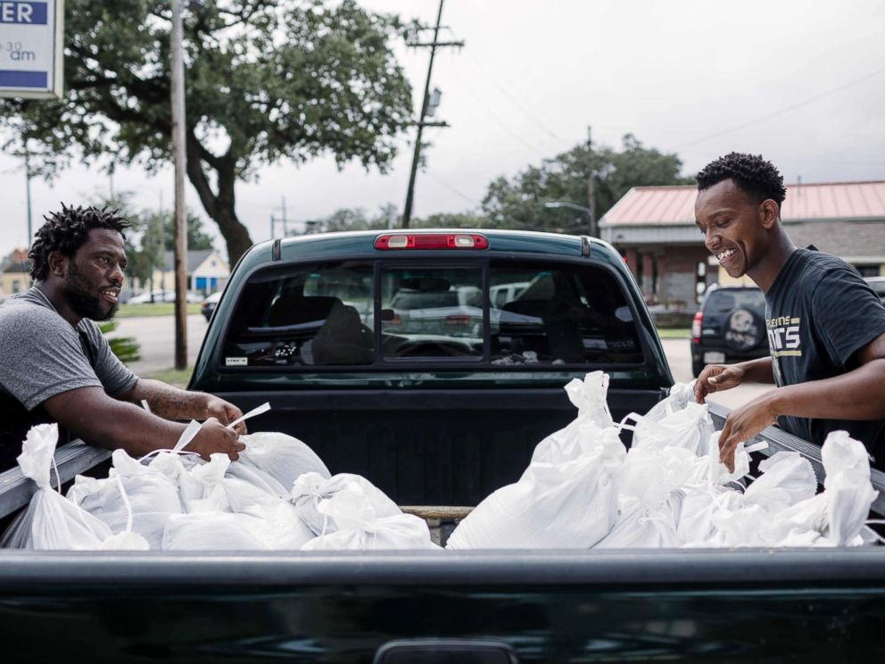 PHOTO: Percy Harrison (L) and Jeramie Moliere load sandbags into the back of a truck to bring to people who live in the neighborhood surrounding their church in preparation for Hurricane Nate in New Orleans, Oct. 7, 2017.