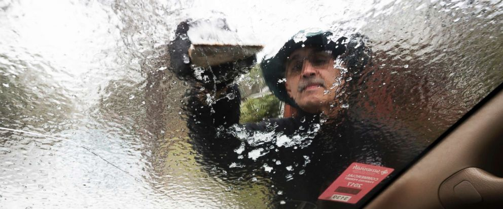 PHOTO: Omar Elkhalidi uses a wood shim to scrape ice off his windshield that accumulated overnight from freezing temperatures, Jan. 3, 2018, in Savannah, Ga.
