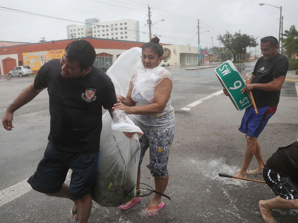 PHOTO: People clear debris out of a drainage ditch in an attempt to keep the area from flooding as Hurricane Irma passes through on Sept. 10, 2017 in Miami.