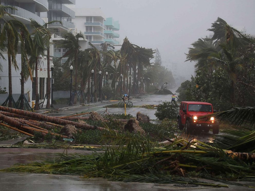 PHOTO: A vehicle passes downed palm trees and two cyclists attempt to ride as Hurricane Irma passes through the area on Sept. 10, 2017 in Miami Beach, Fla.