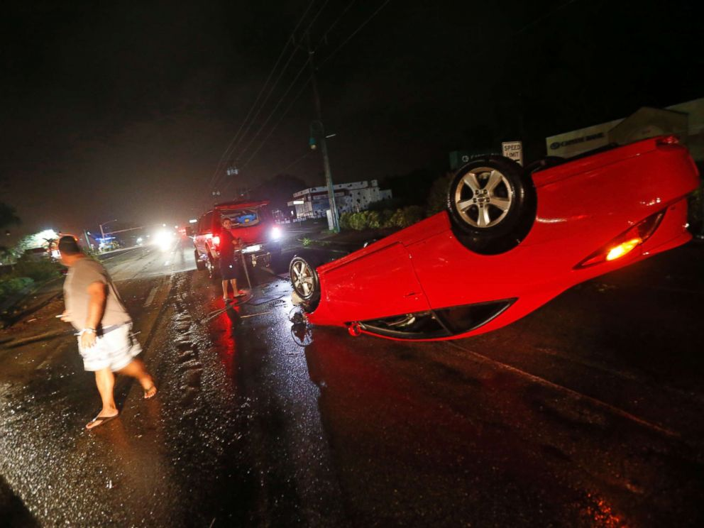 PHOTO: People tend to a car that flipped over on Cape Coral Parkway during Hurricane Irma, in Cape Coral, Fla., Sept. 10, 2017.