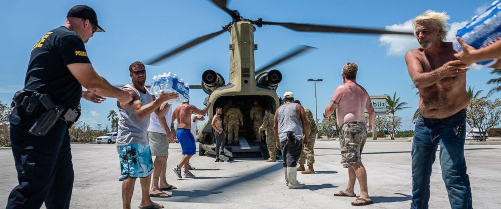 PHOTO: Soldiers with the Florida National Guard and local residents unload relief supplies from a Chinook cargo helicopter in a shopping center parking lot in Key West, Fla., Sept. 13, 2017.