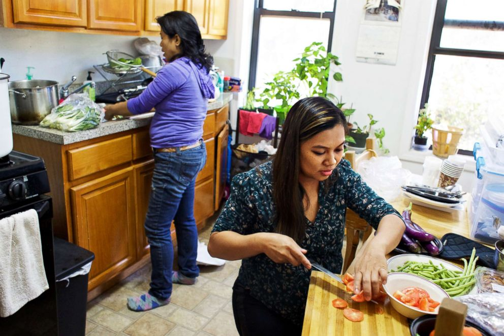 PHOTO: Edith Mendoza, left, and Sherile Pahagas, right, prepare a meal together in the home of Juana Dwyer, Oct. 28, 2017. Mendoza and Pahagas are suing their former employers, a German diplomat and his wife.