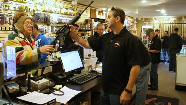 PHOTO: Manager Art Fermanian hands an assault rifle to a customer to look at as other customers pack the Get Some Guns & Ammo store at around 10am on Dec. 21, 2012 in Murray, Utah.