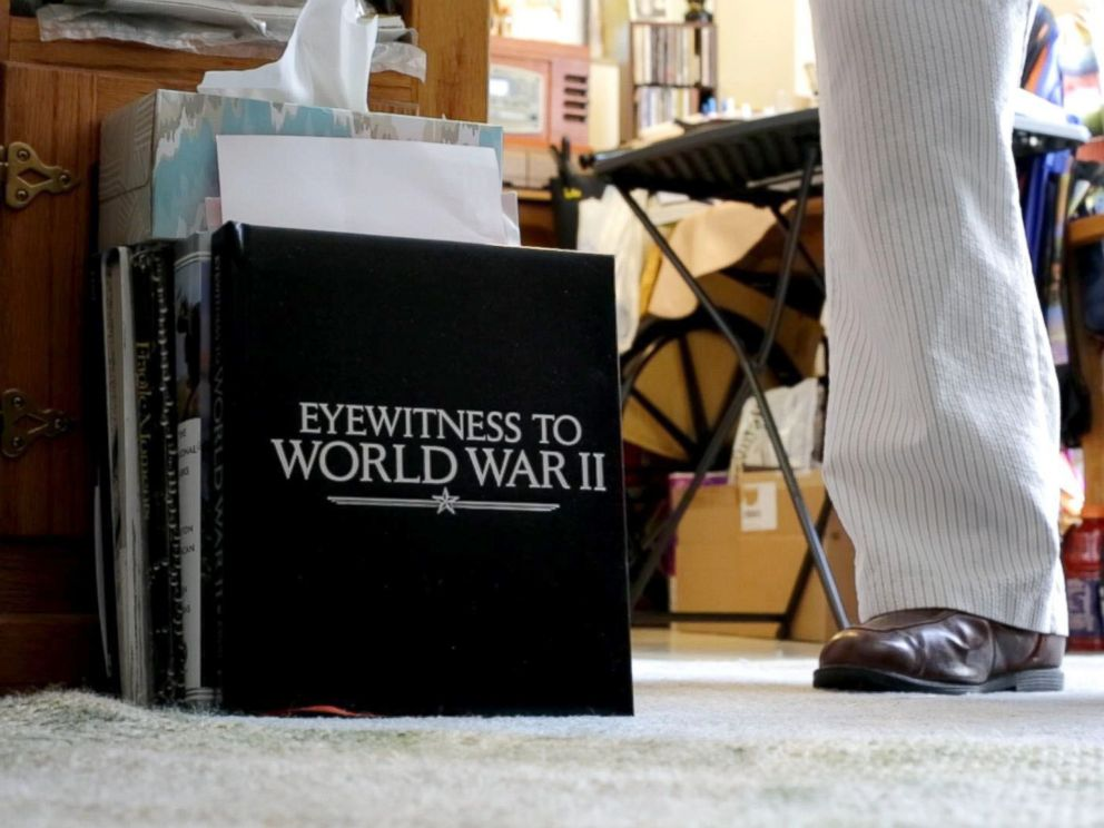 PHOTO: Leatherman stands next to a book on the ground of his apartment that is entitled Witnesses of WWII. Leatherman was a mailman aboard the USS Oglethorpe in the Pacific Theater.