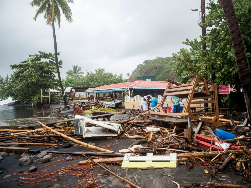 PHOTO: People stand among the debris at a restaurant in Le Carbet, on the French Caribbean island of Martinique, after it was hit by Hurricane Maria, on September 19, 2017.