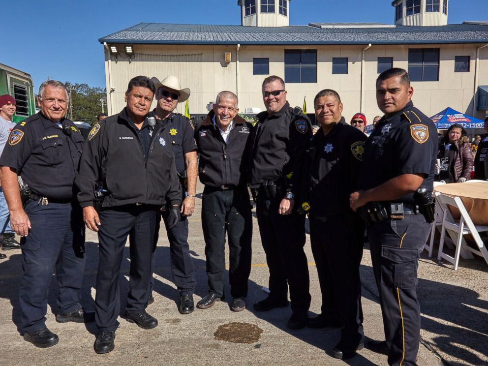 PHOTO: Gallery Furniture owner Jim McIngvale, center, poses with police officers at the free Thanksgiving dinner he hosted in Houston.