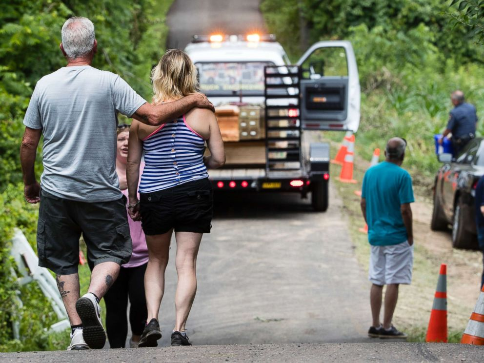 PHOTO: People walk at the entrance to a blocked off drive way, in Solebury, Pa., as the search continues Wednesday, July 12, 2017, for four missing young Pennsylvania men feared to be the victims of foul play.