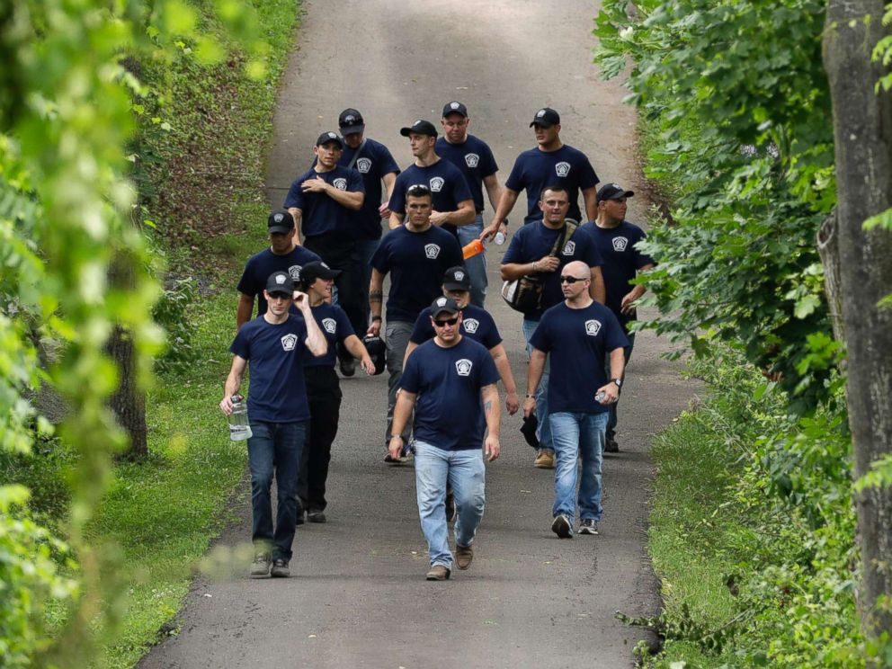 PHOTO: Law enforcement workers walk down a blocked off drive way in Solebury, Pa., as the search resumes Tuesday, July 11, 2017, for four missing young Pennsylvania men.