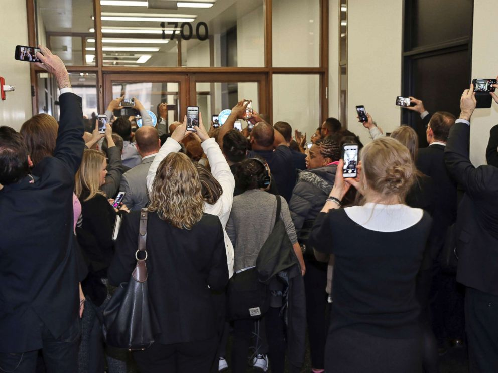 PHOTO: People rush the doors of the jury assembly room as former President Barack Obama arrives for jury duty in the Daley Center on Nov. 8, 2017, in Chicago, Ill. Obama is to be paid the same $17.20 a day that others receive for reporting for jury duty.
