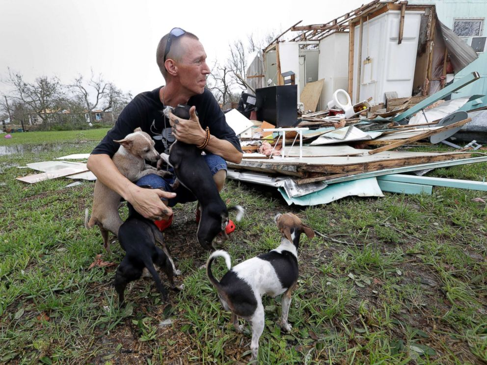 PHOTO: Sam Speights tries to hold back tears while holding his dogs and surveying the damage to his home in the wake of Hurricane Harvey, Aug. 27, 2017, in Rockport, Texas.